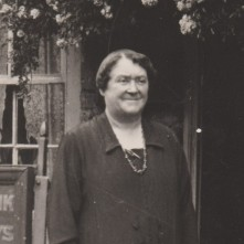 A black and white photo of Agnes Peutrill, a white woman standing outside a Lloyds bank. Light coloured flowers are blooming above the doorway and window of the bank. Her short hair is parted at the side, flat from the root, but curled around her forehead. Her thin eyebrows are knit in the middle as if it is bright out side, and her thin lips are smiling in a way that leaves large crease lines under her cheeks. She is wearing a black collared coat and has a long necklace around her neck.