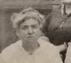 A black and white photo of a white woman with long white hair tied in a messy bun on the top of her head, wearing a white shirt.. Her grey eyebrows are positioned in a slight scowl, framing her dark eyes and large, slightly hooked nose. Her thin lips are also frowning.