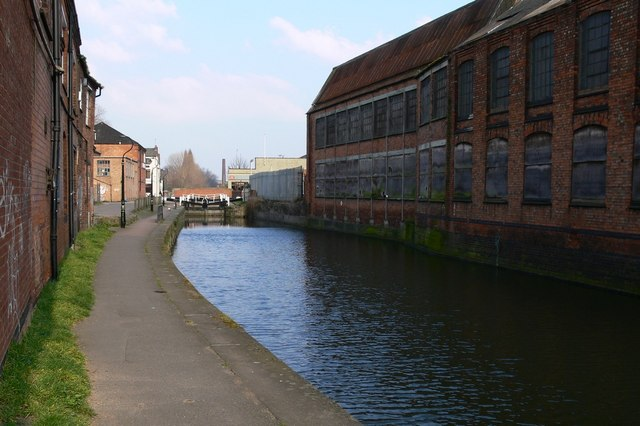 On the right of the photo is a red-brick factory lined with huge windows. Next to the factory is the Grand Union canal. On the left of the photo is the canal tow path. In the distance the North Lock can be seen.